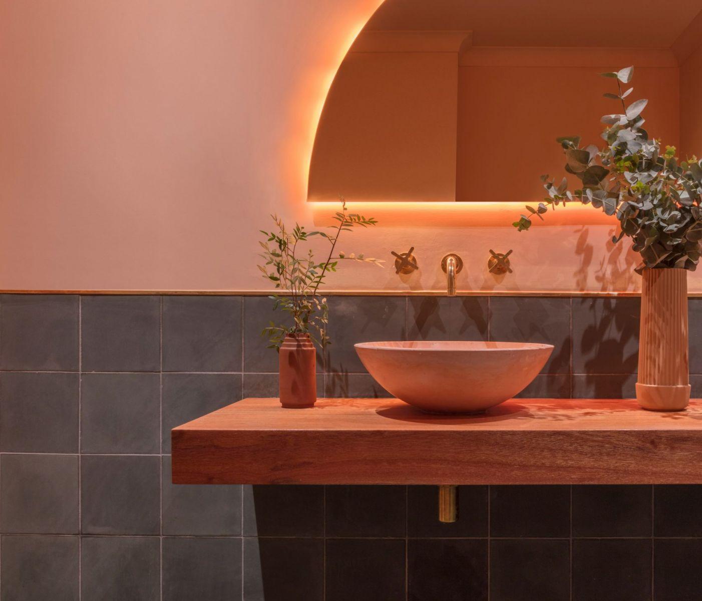 Bồn rửa tay màu hồng đào kết hợp cùng ánh đèn vàng dịu dàng giúp không gian nội thất trở nên ấn tượng