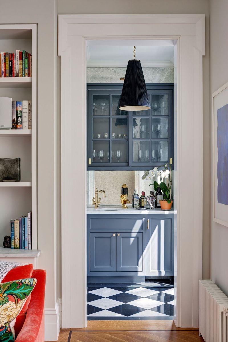 Trong công cuộc phục hưng phong cách Hy Lạp của ngôi nhà này, quầy bar bếp màu xanh làm nằm ngoài khu vực phòng khách được thắp sáng bằng đèn thả hình nón.