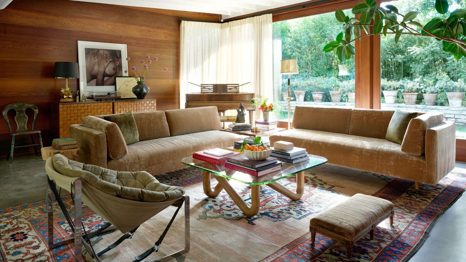 Phòng khách mang đậm phong cách Mid-century. Màu nâu gỗ ấm cúng kết hợp cùng họa tiếtVintage của thảm tạo ra tổng thể vô cùng hài hòa