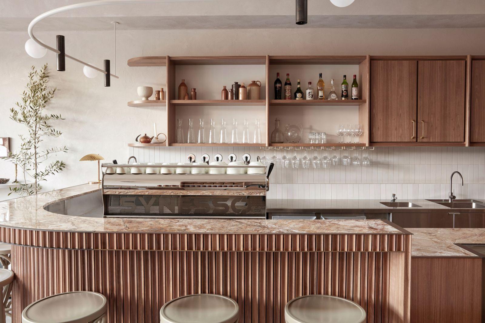 Những chiếc ghế bar cao với sắc xanh banquette đã giúp hoàn thiện bầu không khí ấm cúng và vintage của khu vực này