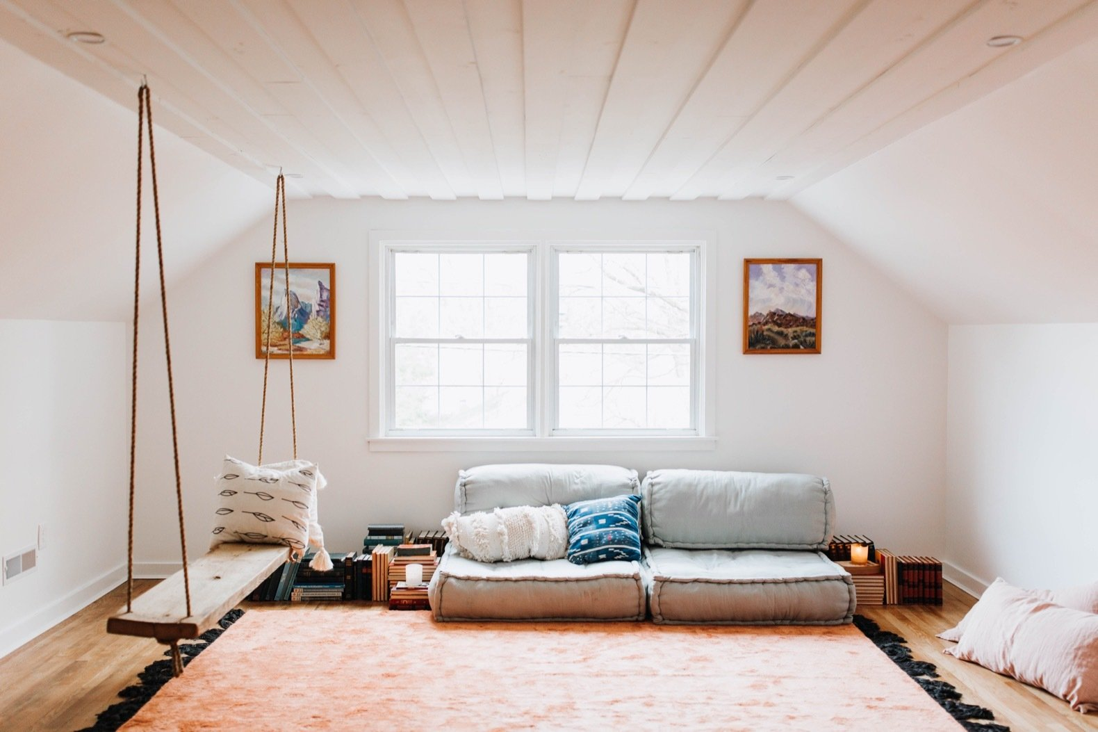 Living Room, Recessed Lighting, Sofa, Medium Hardwood Floor, Bench, and Rug Floor A limited budget restricted what Chris and Claude could do to the attic, but they managed to refinish the floors, change the lighting, and repaint the walls Chantilly Lace by Benjamin Moore.