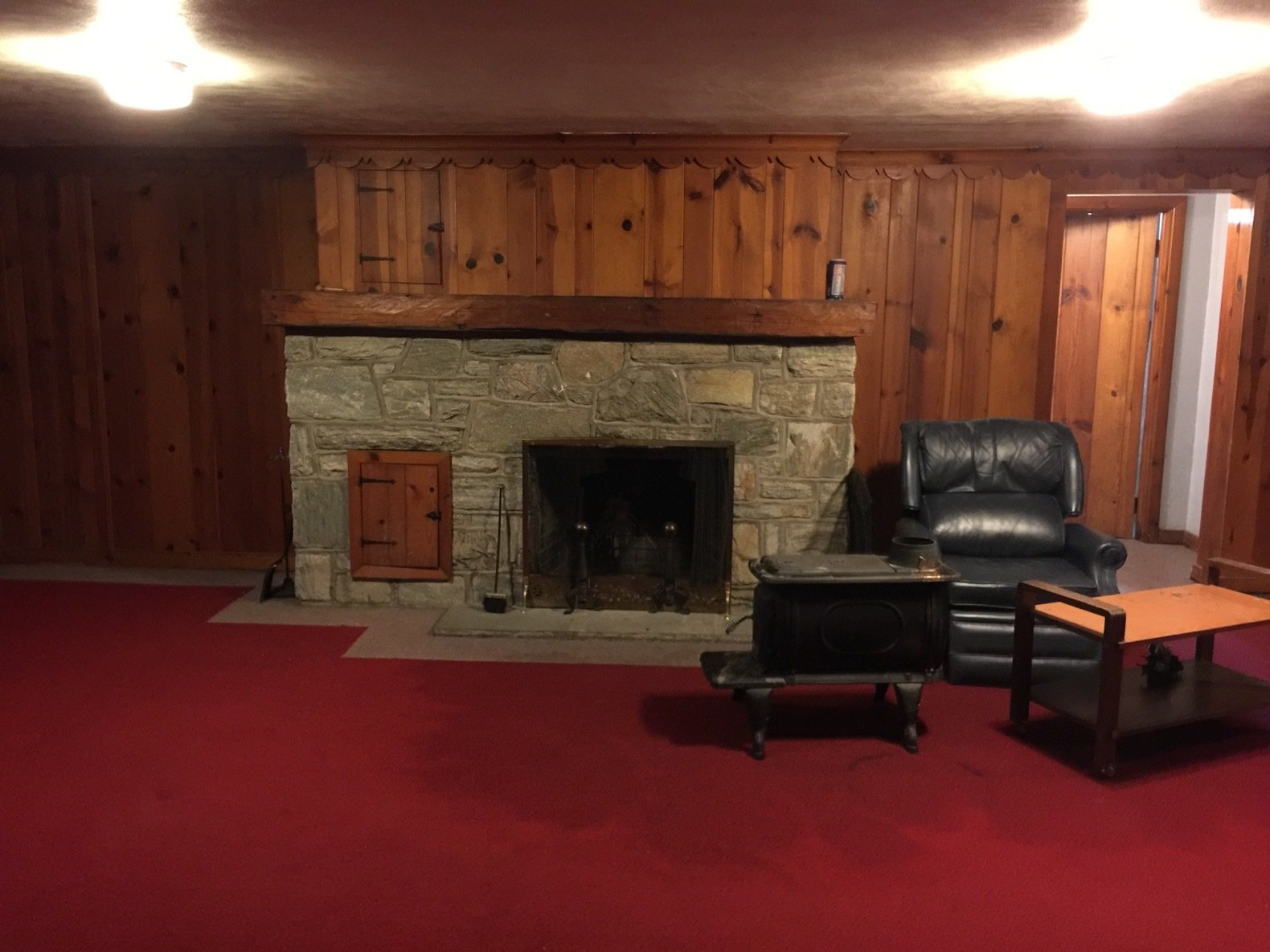 Dated wood paneling and stone surround were part of the original basement.