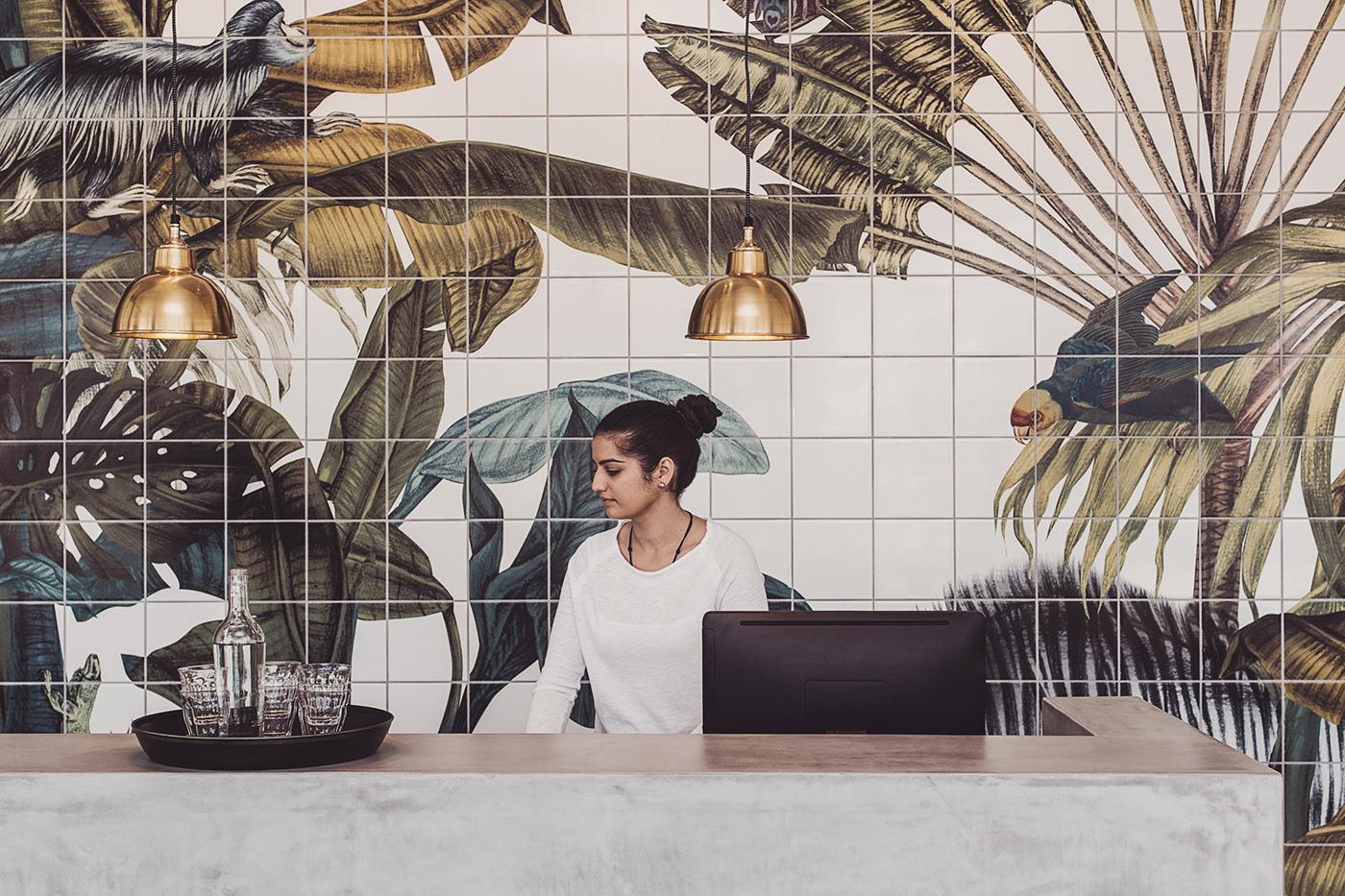 Bức tường phía sau bàn tiếp tân được trang trí bằng bức tranh làm từ gốm vô cùng tinh xảo, gợi nhớ hình ảnh của thiên nhiên nhiệt đới.